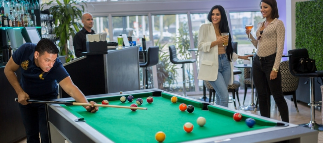 A man and two women playing pool near the bar