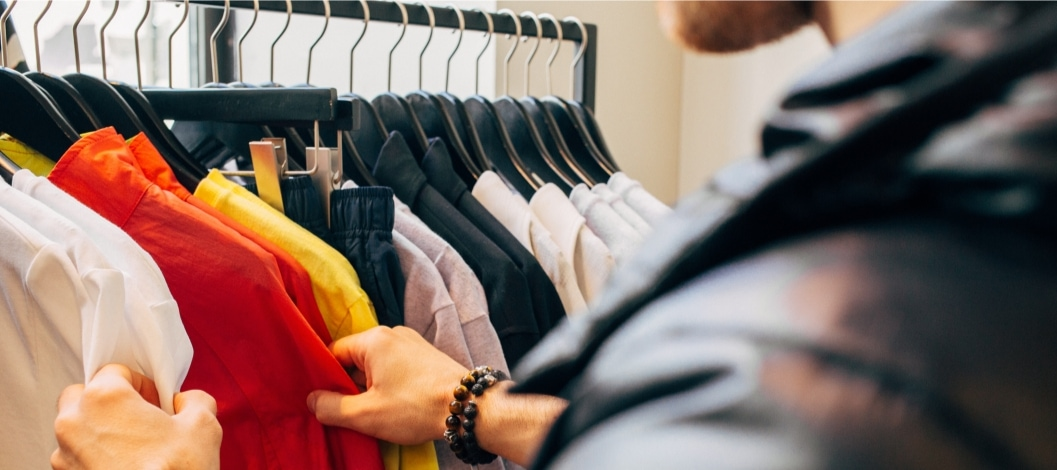Man looking through clothes on a rack