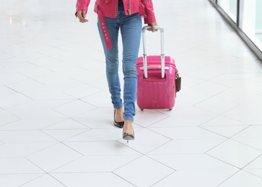Woman pulling a piece of pink luggage through an airport