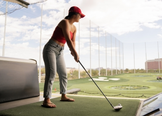 Woman golfing at a driving range