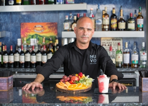 Bartender serving a plate of fruit and a frozen drink