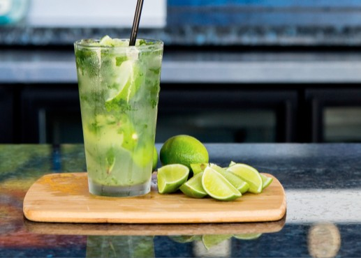 Mojito and lime slices sitting on a wooden board on a bar