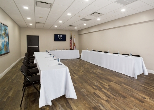 Conference room with 3 long tables with white tablecloths and black folding chairs