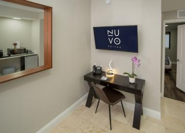 Desk in corner with flat screen TV and mirror